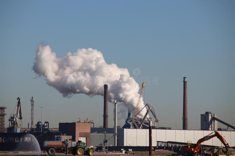 Lot of water vapor coming out of the chimney of ENCI concrete and cement factory in IJmuiden and Velsen. stock photos