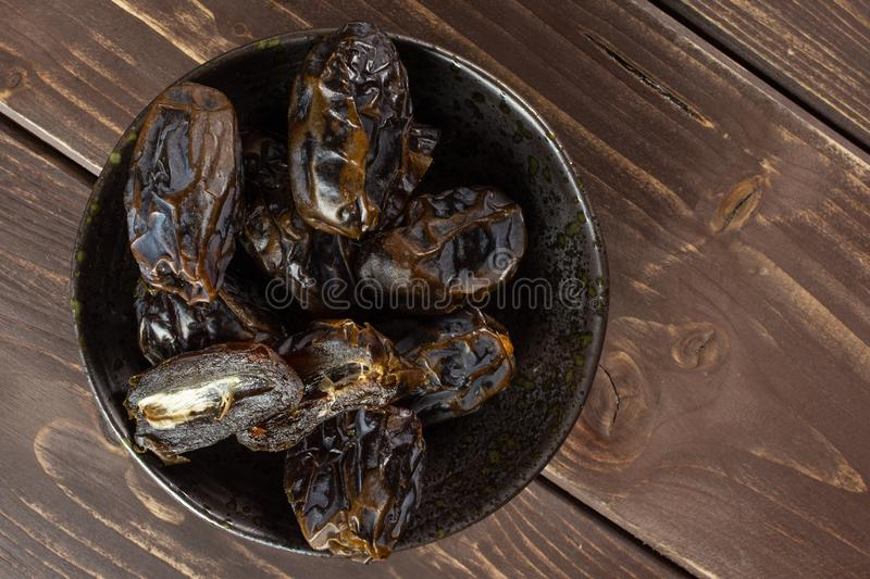 Dried date medjool on brown wood. Lot of whole dried brown date medjool on grey ceramic plate flatlay on brown wood stock photo