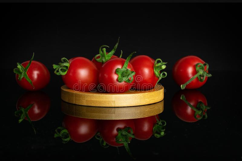 Red cherry tomato isolated on black glass stock images