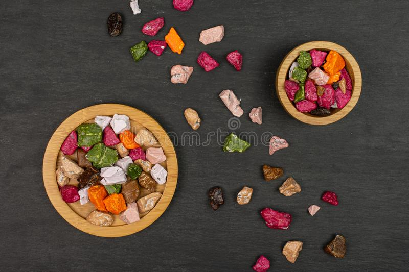 Chocolate stone candy on grey stone. Lot of whole sweet chocolate stone on bamboo coaster in tiny wooden bowl flatlay on grey stone stock photography