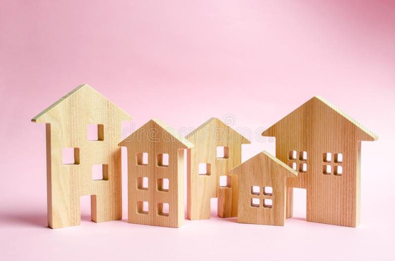 A lot of wooden houses on a pink background. The concept of the city or town. Investing in real estate, buying a house. Management stock photos