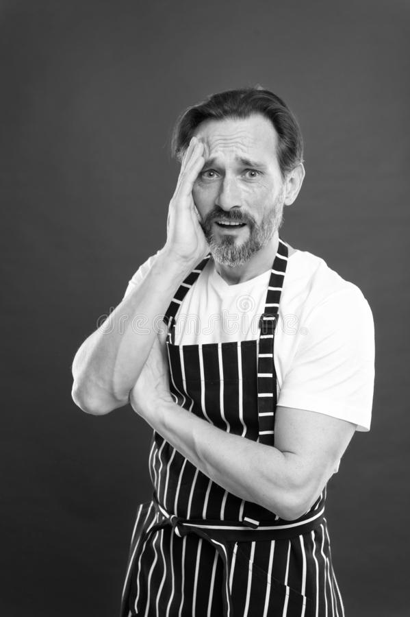 Lot of work. Confident mature handsome man in apron red background. He might be baker gardener chef or cleaner. Good in. Everything. Professional occupation royalty free stock photo