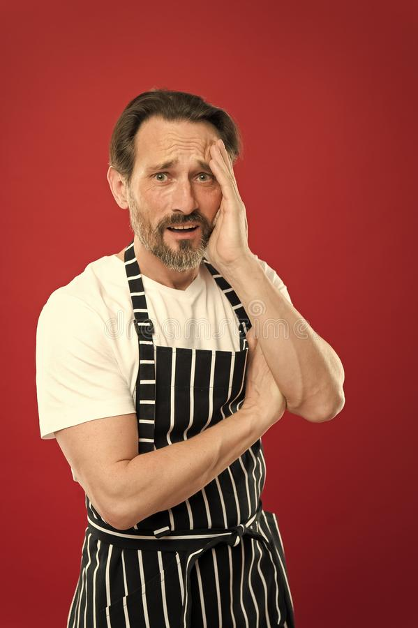 Lot of work. Confident mature handsome man in apron red background. He might be baker gardener chef or cleaner. Good in. Everything. Professional occupation royalty free stock photography