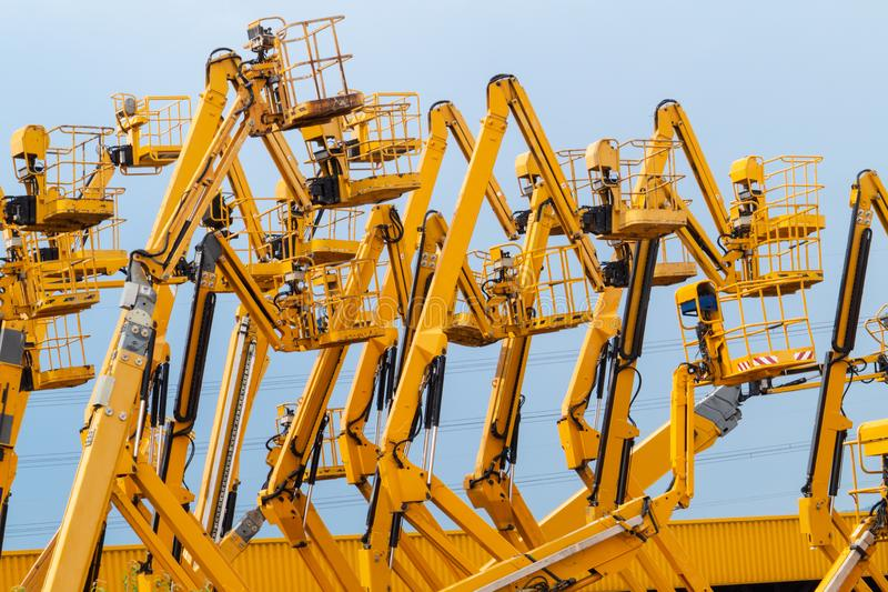 Lot of yellow articulating boom lifts. Lot of articulating boom lifts. Construction equipment manufacturing royalty free stock photo