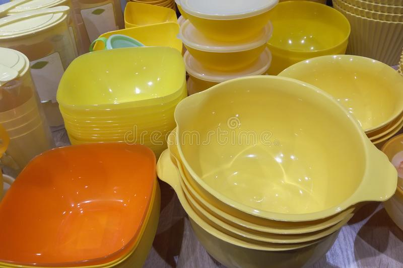 A lot of yellow bright plastic bowls and boxes kitchenware on a table. Close up stock image