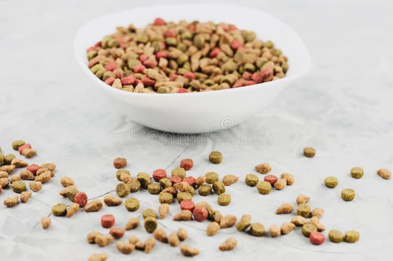 Lote da comida de gato colorida seca na bacia cerâmica branca e em muitas pelotas dispersadas foto de stock royalty free