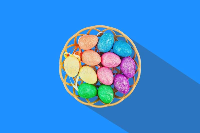 Lote de ovos artificiais coloridos e efervescentes na cesta de vime marrom com sombra dura longa no centro da tabela azul Vista d fotografia de stock