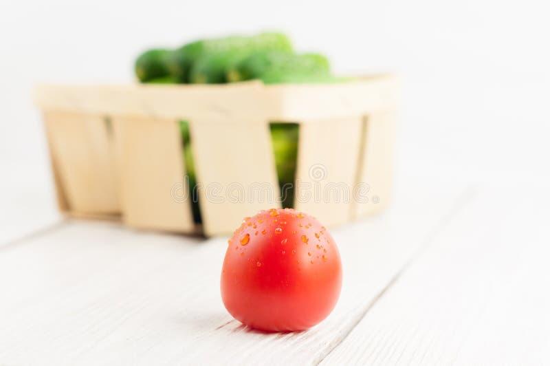 Lote de pepinos verdes frescos na cesta de vime e no único tomate maduro vermelho no fundo de madeira branco imagem de stock royalty free
