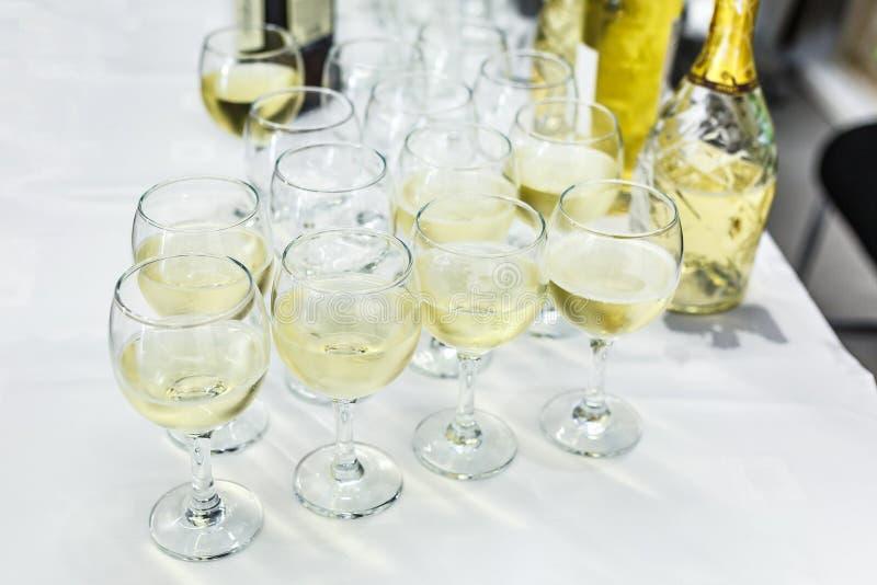 Lote de vidros borrados com champanhe na tabela do partido de recepção fotos de stock