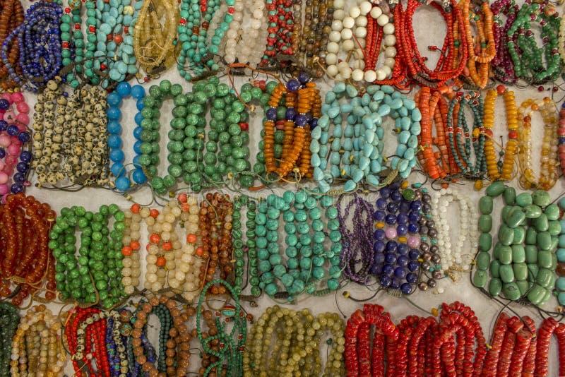 Lote dos braceletes multi-coloridos brilhantes feitos das bolas das pedras que encontram-se na superfície branca da tabela handma foto de stock royalty free