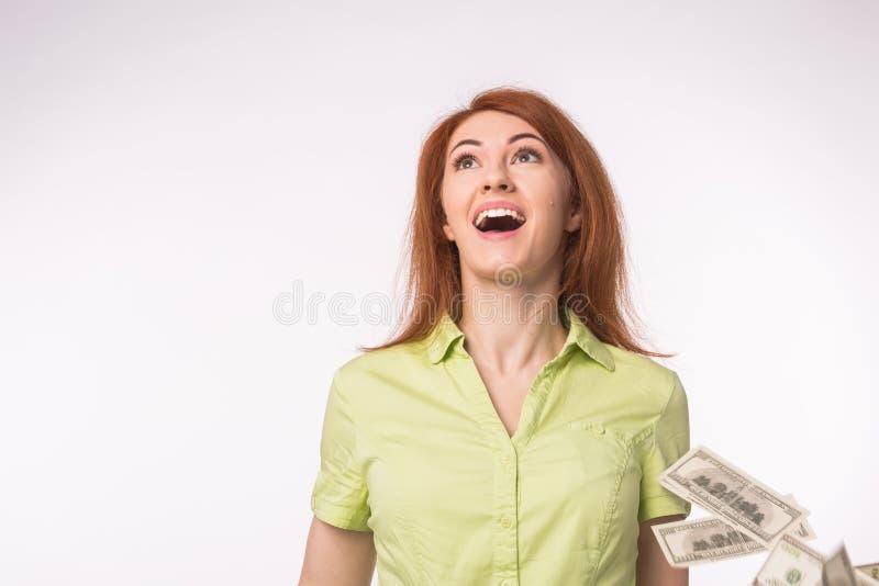 Lotería, concepto financiero del éxito - mujer emocionada que se coloca debajo de la lluvia del dinero sobre el fondo blanco imágenes de archivo libres de regalías