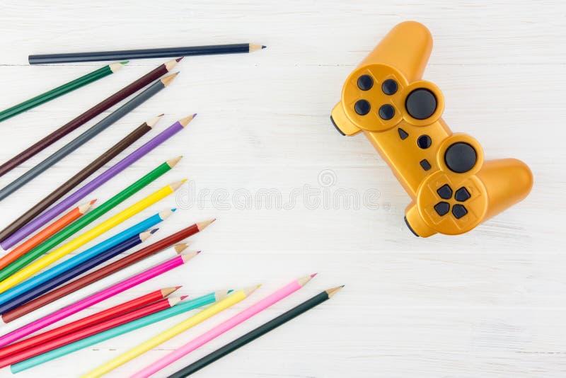 Lotes de lápis coloridos ao lado do manche alaranjado do jogo no Whit imagens de stock
