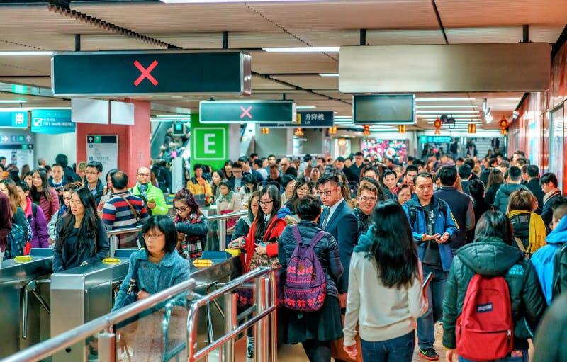 Lotes do povo chinês ocupado que aglomera-se na estação de metro de Tsim Sha Tsui em Hong Kong fotos de stock