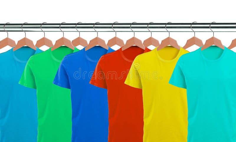 Lotes dos t-shirt nos ganchos isolados no branco fotos de stock