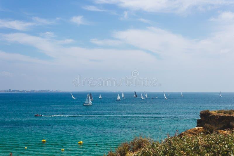Lotes dos veleiros que navegam no oceano perto da costa de Lagos foto de stock