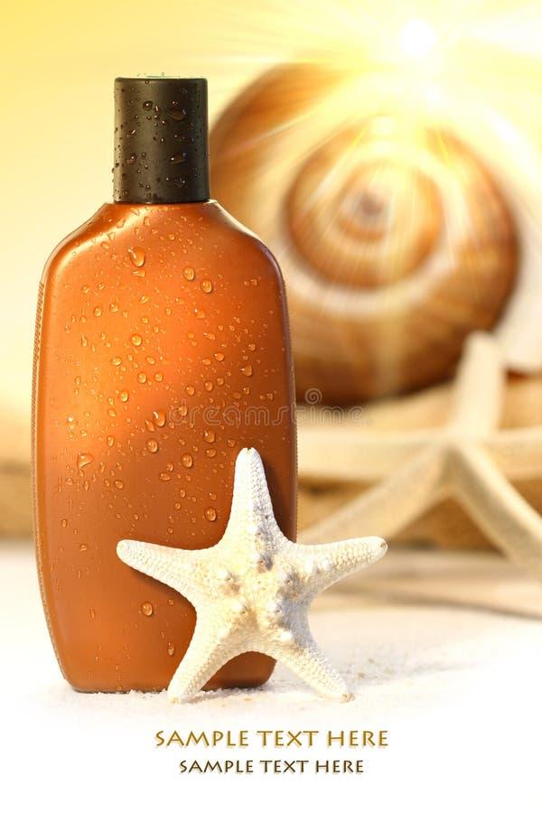Lotion de bronzage avec des seashells photos stock