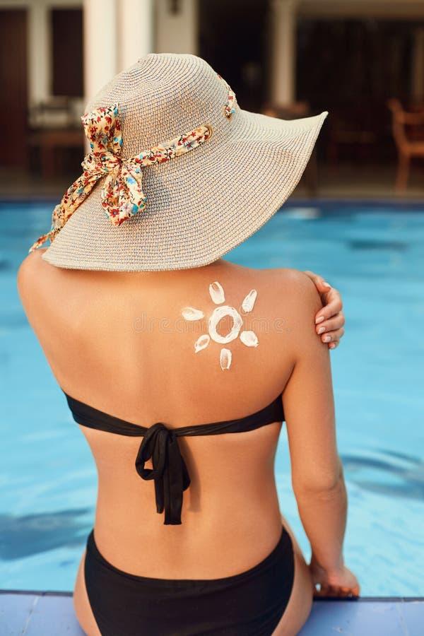 Lotion de bronzage Jeune femme sexy dans le bikini appliquant la crème solaire de protection solaire Protection de Sun Cr?me de S photo stock