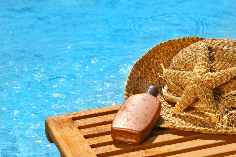 Lotion et chapeau de paille de bronzage photo stock