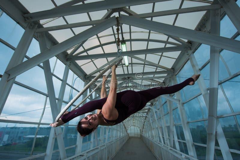 Lotnicza gimnastyczka robi rosjaninowi rozłamom kratownicowi na lotniczym obręczu zawieszającym na metalu cyrkowa aktorka na p obraz stock