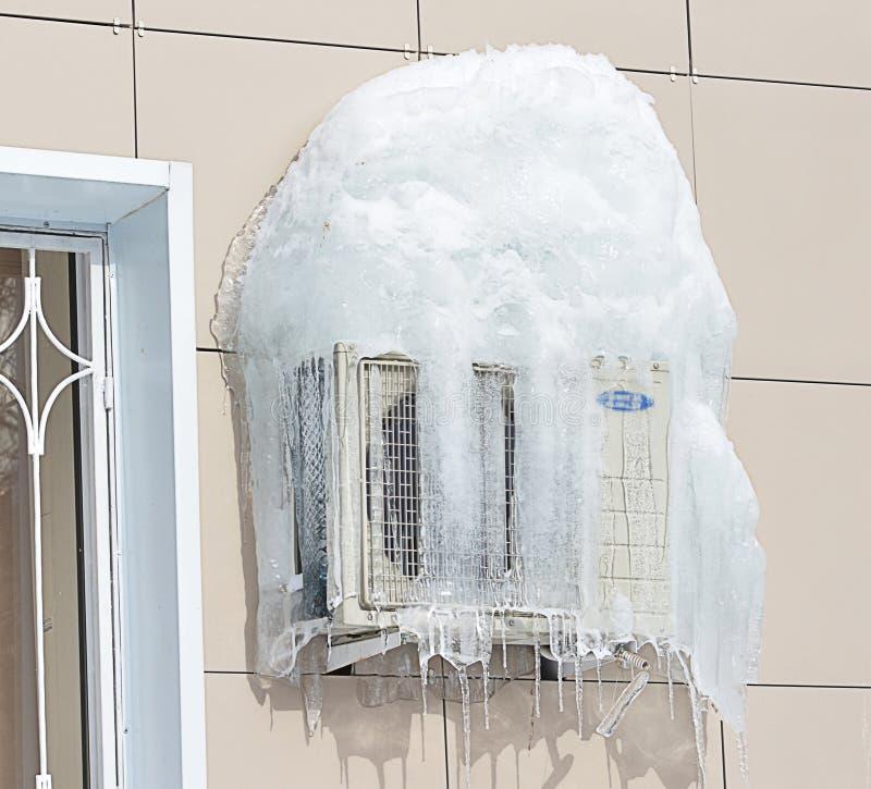 Lotniczy conditioner zakrywający z zamarzniętym lodem i soplami koło okna fotografia stock
