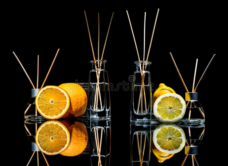 Lotniczy fresheners w szkle zgrzytają z kijami, cytryna, zielony jabłko i pomarańcze z odbiciem odizolowywającym na czarnym tle, zdjęcie stock