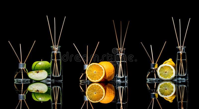 Lotniczy fresheners w szkle zgrzytają z kijami, cytryna, zielony jabłko i pomarańcze z odbiciem odizolowywającym na czarnym tle, fotografia stock