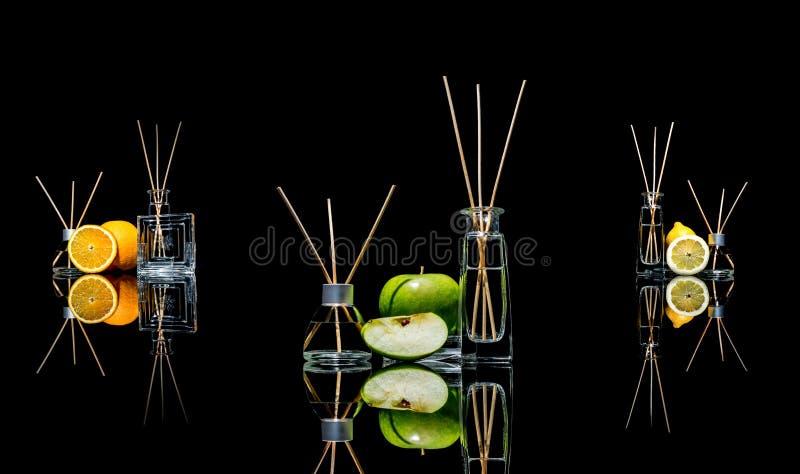 Lotniczy fresheners w szkle zgrzytają z kijami, cytryna, zielony jabłko i pomarańcze z odbiciem odizolowywającym na czerni, fotografia stock