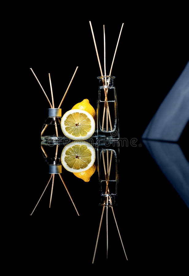 Lotniczy fresheners z cytryny perfumowaniem w pięknym szkle zgrzytają z kijami, całą cytryna i plasterek cytryna z odbiciem zdjęcie stock