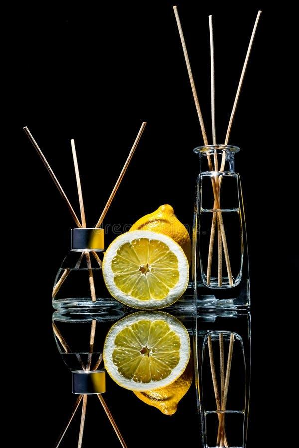 Lotniczy fresheners z cytryny perfumowaniem w pięknym szkle zgrzytają z kijami, całą cytryna i plasterek cytryna z odbiciem fotografia royalty free