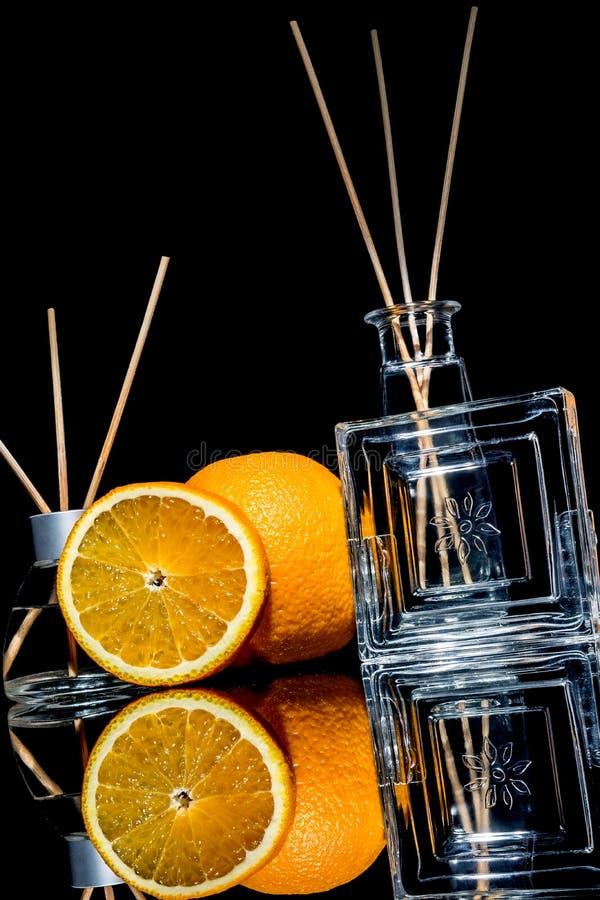 Lotniczy fresheners z pomarańczowymi owoc czują w pięknych szklanych słoje z i plasterek pomarańcze kijami i całą pomarańcze zdjęcia stock