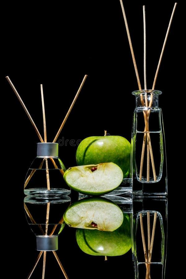 Lotniczy fresheners z zielonym jabłczanym perfumowaniem w pięknym szkle zgrzytają z kijami, całym zielonym jabłko i plasterek jab fotografia stock