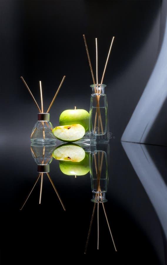Lotniczy fresheners z zielonym jabłczanym perfumowaniem w pięknym szkle zgrzytają z kijami, całym zielonym jabłko i plasterek jab fotografia royalty free