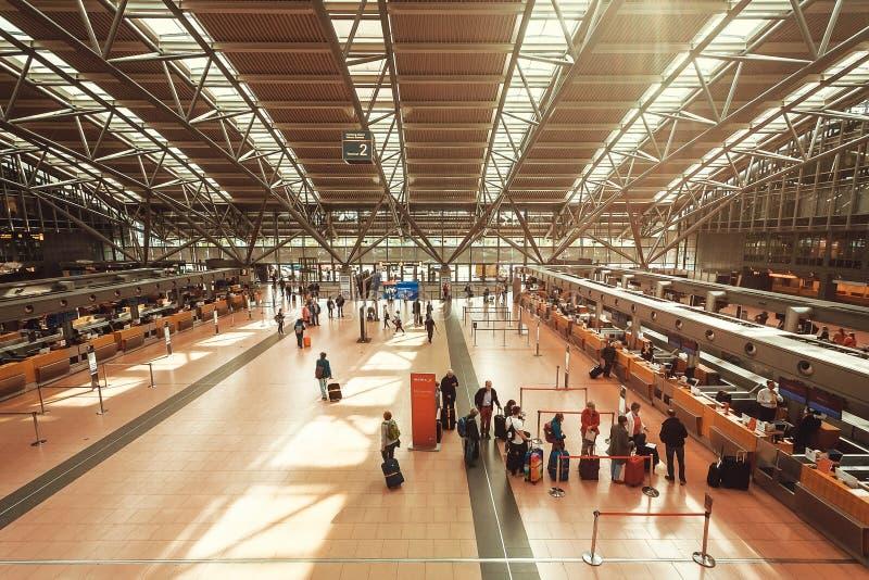 Lotniskowi pasażery stoi przy odprawa kontuarem w ogromnej przestrzeni dla odjeżdżać podróżników fotografia stock