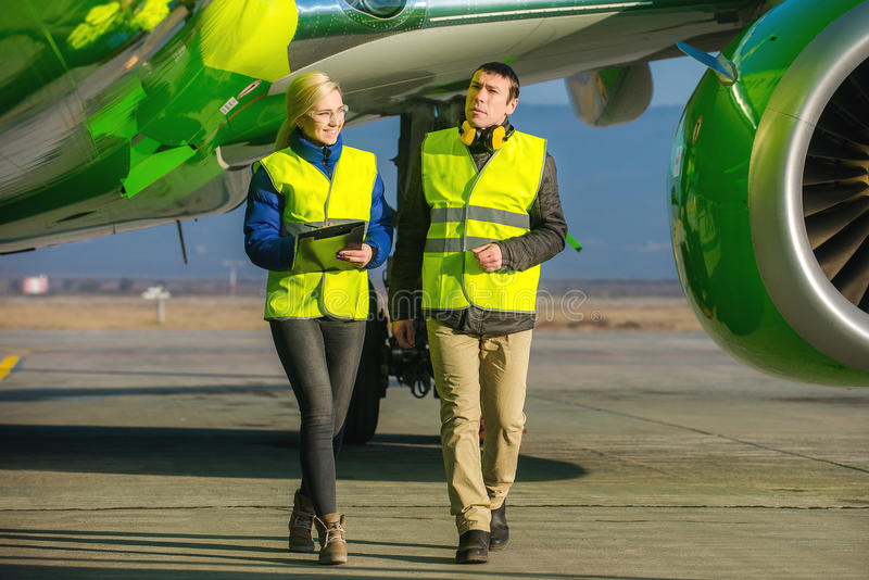 Lotniskowi pracownicy obchodzi się samolot fotografia stock