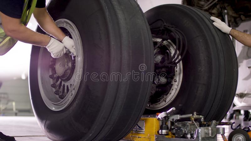Lotniskowy pracownik sprawdza podwozie Silnik i podwozie pasażerski samolot pod ciężkim utrzymaniem Inżynierów czeki obraz royalty free