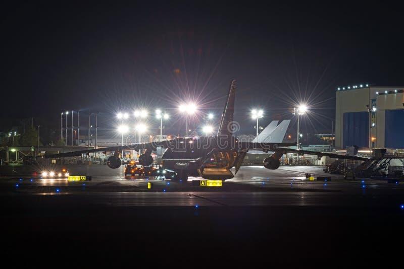 Lotniskowych operacj ładunku samolotu ciężki rozładunek przy nocą zdjęcia stock
