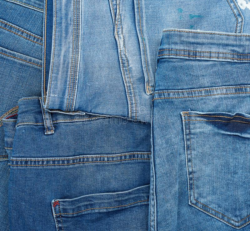 Lots of blue classic jeans stacked chaotically, back pocket royalty free stock image