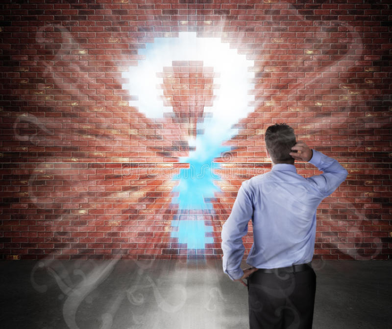 Lots of business questions. Confused businessman standing in front of a brick wall with question mark hole and question marks flying into the room royalty free stock images