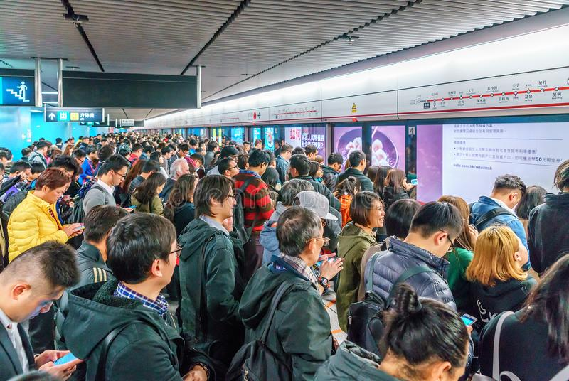 Lots of busy Chinese people crowding at subway station in Central District of Hong Kong waiting for a train to arrive royalty free stock images