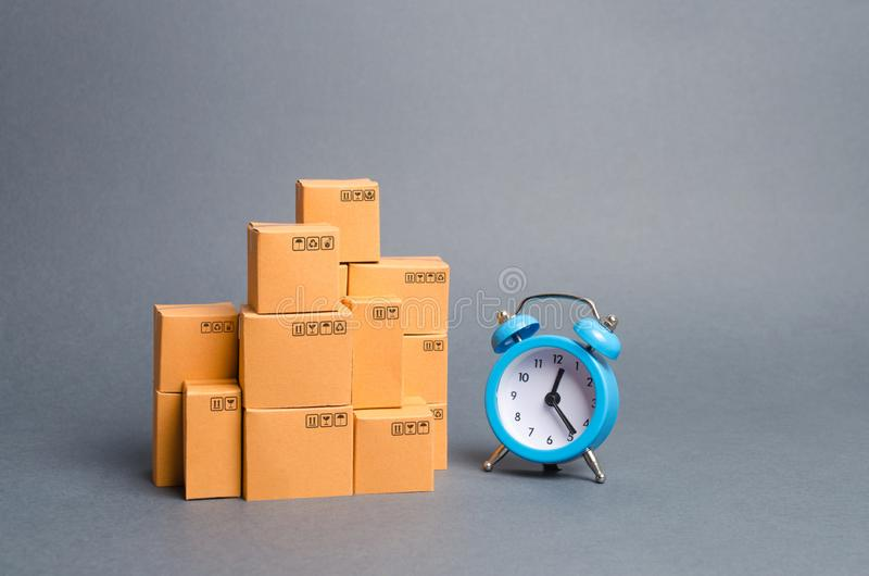 Lots of cardboard boxes and a blue alarm clock. Express delivery concept. Temporary storage, limited offer and discount royalty free stock photo