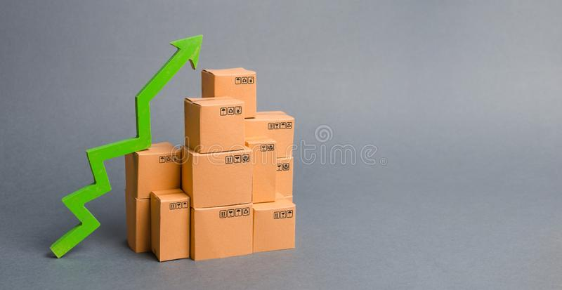 Lots of cardboard boxes and a green arrow up. growth rate of production goods, raise economic indicators. Increasing consumer. Demand. exports and imports stock photography