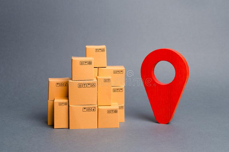 Lots of cardboard boxes and a red position pin. Locating packages and goods. Tracking parcels by the Internet. Algorithm royalty free stock photos