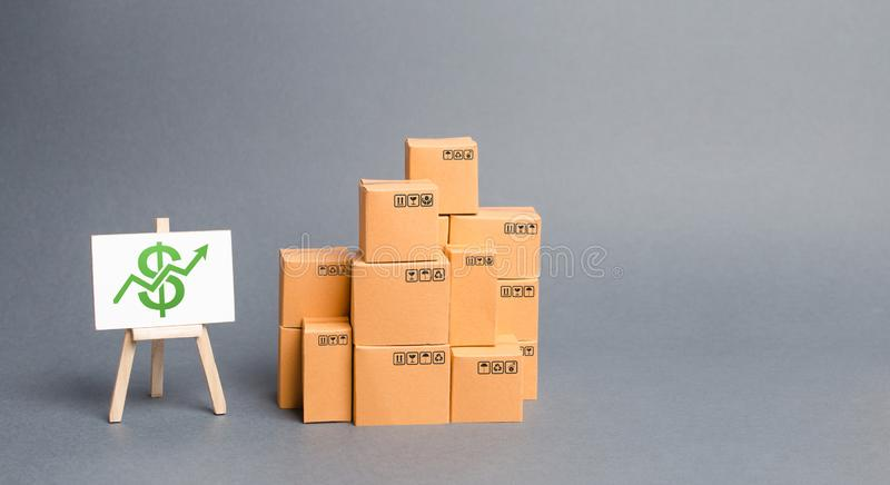 Lots of cardboard boxes and stand with green up arrow. Growth of income from the sale of goods. Price increase. The growth rate. Of production. Increasing stock photo