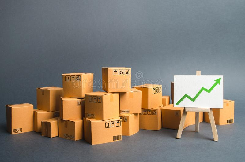 Lots of cardboard boxes and a stand with a green up arrow. rate growth of production of goods and products, increasing economic. Indicators. Increasing consumer stock image