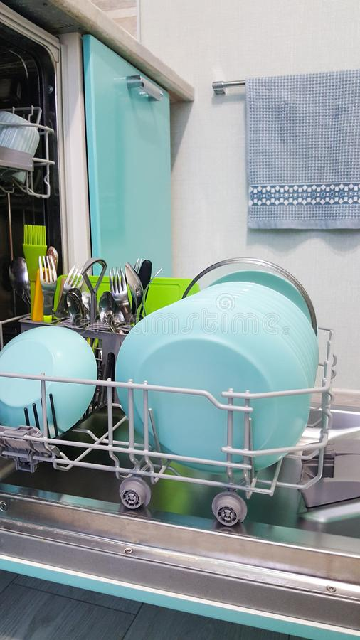 Lots of clean blue plates and cutlery in an open dishwasher, side view stock image