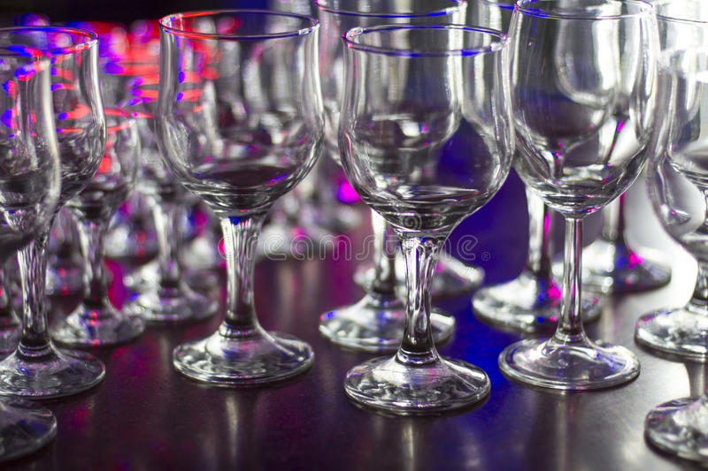 Lots of clean empty glasses of drinks on the bar in a nightclub. Glare and reflections on the glasses in the dark stock image