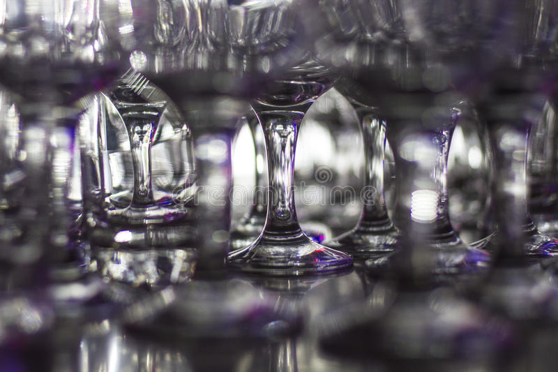 Lots of clean empty glasses of drinks on the bar in a nightclub. Glare and reflections on the glasses in the dark royalty free stock photography