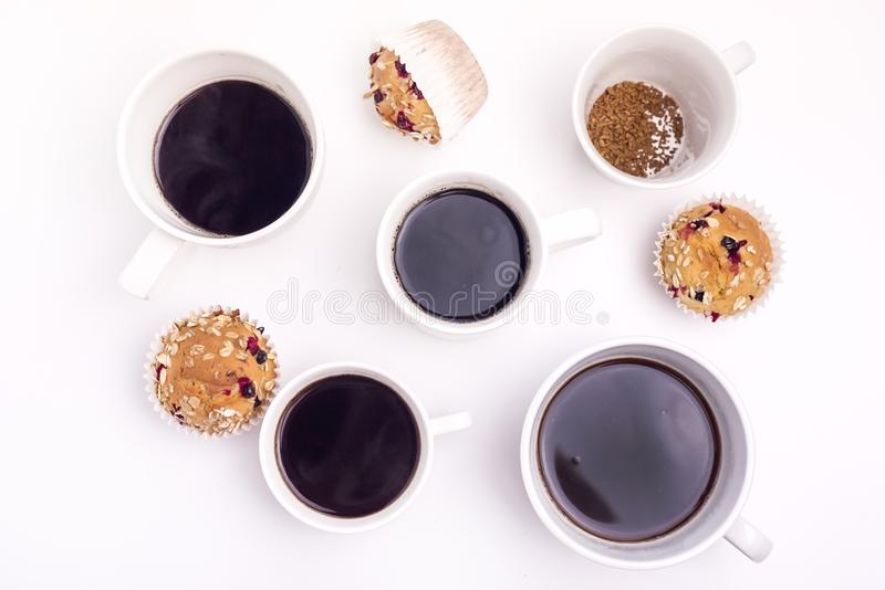 Lots of Coffee Cups on White Background Muffins CupCakes Top View Breakfast Time Concept Flat Lay royalty free stock photo