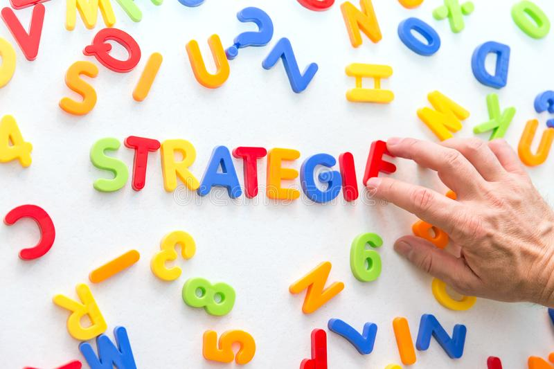 Lots of colorful letters, hand building german word, strategy royalty free stock images