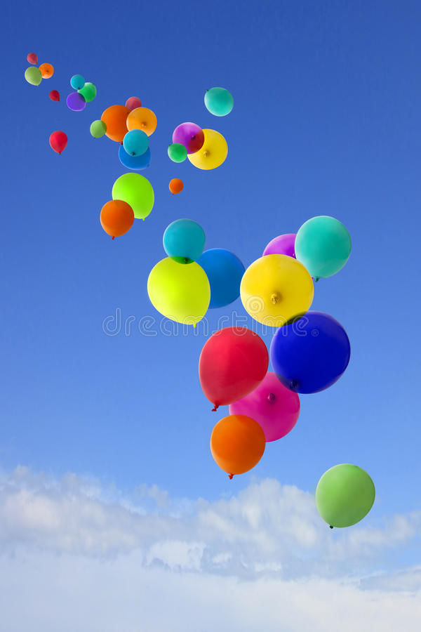 Lots of coloured balloons flying into the sky stock images